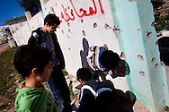 Children look for bullets in the wall of a shot out building across from the military base in Benghazi on March 1, 2011.