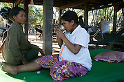 Kruu, bush doctor, Larg Hoch, who sells her herbs and plants at Tbeang Meanchey market. Gathering and preparing DhamChom Pong, a type of sapling, cut and boiled, then given to mothers before and after birth of child. Here pictured with her daughter administering the traditional medicine. Unfortunately her daughter Nut Saroem aged only 20 years old. Was suffering severe preeclampsia and at 8 months pregnant was refered to a clinic by Koeun. The baby was premature, and both lives were saved by Koeun's intervention...Touth Koeun, an ex-Khmer Rouge child soldier turned midwife and trainer, is on the frontline again, but this time campaigning on maternity issues, in Preah Vihear province, Cambodia. The country experiences an extraordinarily high incidence of infant and maternal mortality. The Preah Vihear province, in Cambodia's north, bordering on the Thai border, can be described as an outback rural area, villages often many hours away from a health centre or clinic, and sometimes near the frontline where soldiers and their families are living. Here, Touth Kouen, a locally much respected pioneer and experienced in maternity issues, trains indigenous women, known as 'Traditional Birth Attendants' (TBA's), correct procedures to assist midwives and nurses, to give direct support to mothers and their babies, during ante and post natal periods. Traditional bush medicine and spiritual practices by 'Kruu' bush doctors, involving the killing of endangered species, gathering herbs and plants, whose burnt remains are often ground up into unhealthy potions, and fed to mothers as miracle cures, and postpartum heating, can cause illness and death. The Kruu, and local people in general need to be re-educated, so as to create a healthy nurturing environment for mothers and their babies. Preah Vihear Province, Cambodia