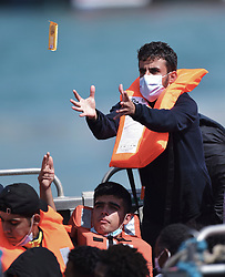© Licensed to London News Pictures. 5/08/2021. Dover, UK. A  migrant prepares to catch a snack bar thrown to him onboard a Border Force vessel at Dover Harbour in Kent after crossing the English Channel. Hundreds of migrants have made the crossing in recent weeks. Photo credit: Stuart Brock/LNP