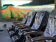 a row of empty massage chairs with a light box of a landscape view with flowers