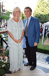 Actor ROBERT POWELL and his wife BABS at a garden party at the Goring Hotel, Beeston Palce, London SW1 to celebrate the unveiling of a bronze bust the late Queen Elizabeth the Queen Mother on 20th July 2004.