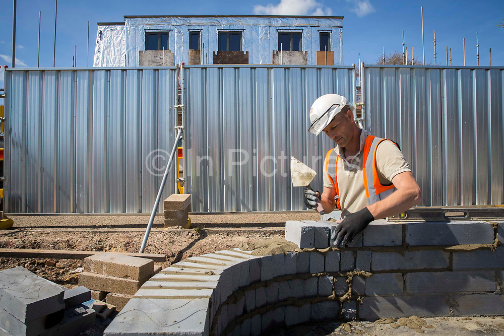 A builder uses a trowel and a spirit level to lay the first bricks with cement onto the foundations of a new house on a home building construction site in Norwich. Norfolk. United Kingdom