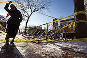 A passerby lifts police tape to traverse the sidewalk on Cedar Avenue across the street from the site of the New Year's Day fire January 4, 2014. Crews continued to clear the area where the building has been demolished, opening some previously restricted surrounding areas.
