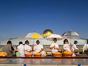 """02 JANUARY 2015 - KHLONG LUANG, PATHUM THANI, THAILAND: People wait for monks to walk past them at Wat Phra Dhammakaya at the start of the 4th annual Dhammachai Dhutanaga (a dhutanga is a """"wandering"""" and translated as pilgrimage). More than 1,100 monks are participating in a 450 kilometer (280 miles) long pilgrimage, which is going through six provinces in central Thailand. The purpose of the pilgrimage is to pay homage to the Buddha, preserve Buddhist culture, welcome the new year, and """"develop virtuous Buddhist youth leaders."""" Wat Phra Dhammakaya is the largest Buddhist temple in Thailand and the center of the Dhammakaya movement, a Buddhist sect founded in the 1970s.   PHOTO BY JACK KURTZ"""