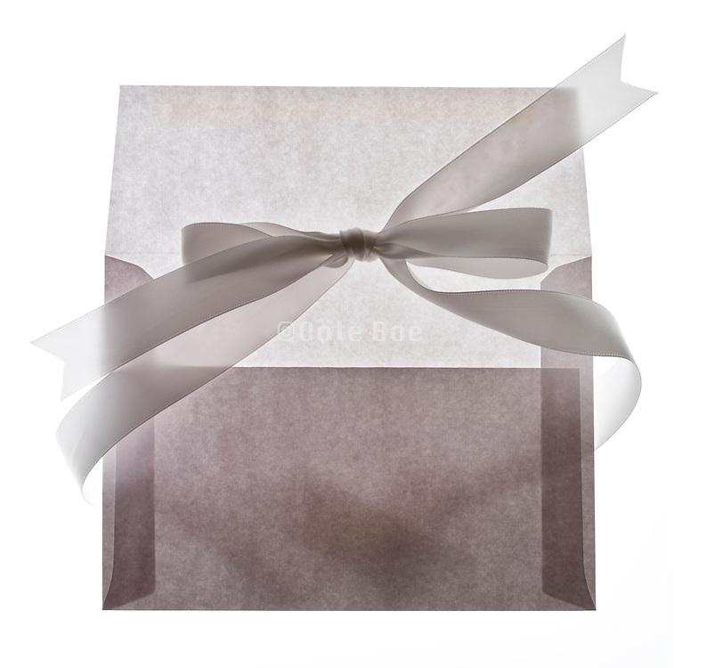 white bow ribbon around a envelope