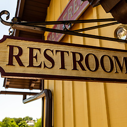 A hanging restrooms sign on a wrought iron bracket.
