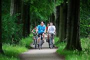 In Soest rijdt een gezin op de fiets door de bossen.<br /> <br /> In Soest a family is cycling at the woods.