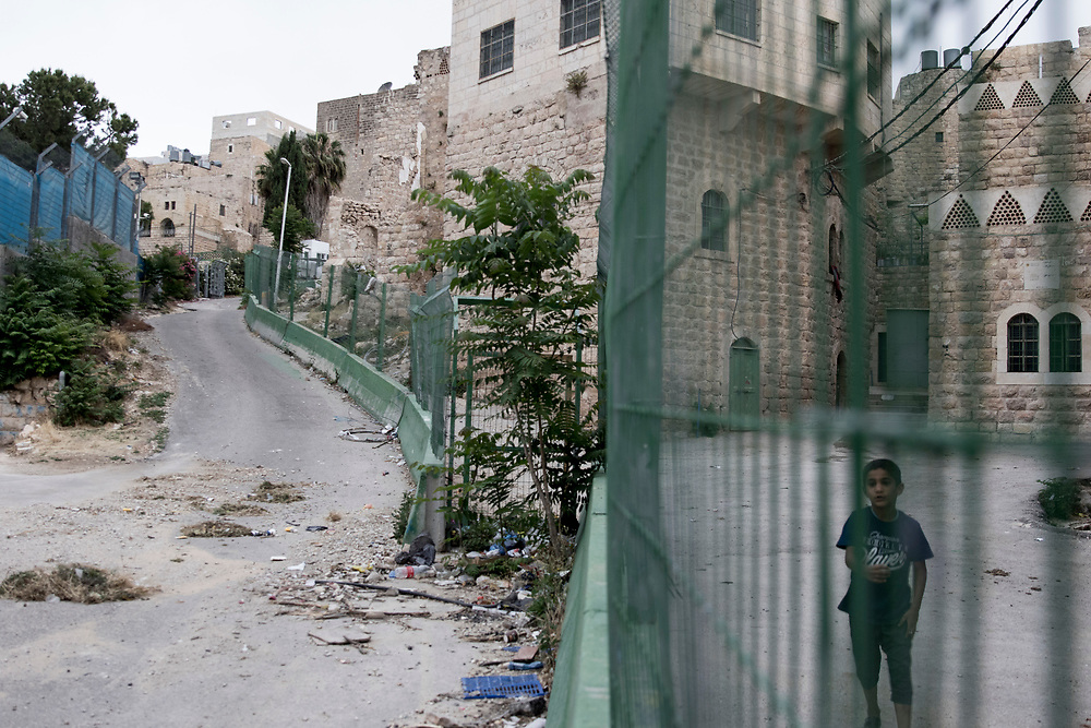 A young boy looks from behind a fence - Palestinians are not allowed to walk on the left side of the street while Israeli settlers roam freely and even carry weapons