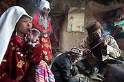 Ikhbal, wife of deceased Abdul Rashid Khan, smoking a cigarette..Inside Mustafa Qol's house..At the camp of Tash Seri (Mustafa Qol's camp)...Trekking through the high altitude plateau of the Little Pamir mountains, where the Afghan Kyrgyz community live all year, on the borders of China, Tajikistan and Pakistan.