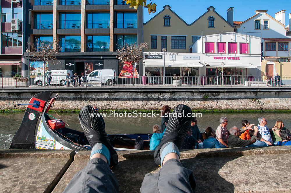 first person view of Tourists on a colourful boat (moliceiro) on a canal in Aveiro, Portugal