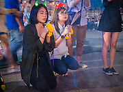 31 DECEMBER 2014 - BANGKOK, THAILAND:  Women wearing their New Year's hats pray on New Year's Eve at Erawan Shrine in Bangkok. Hundreds of thousands of people pack into the Ratchaprasong Intersection in Bangkok for the city's annual New Year's Eve countdown. Many Thais go the Erawan Shrine and Wat Pathum Wanaram near the intersection to pray and make merit before going to their New Year's parties.   PHOTO BY JACK KURTZ
