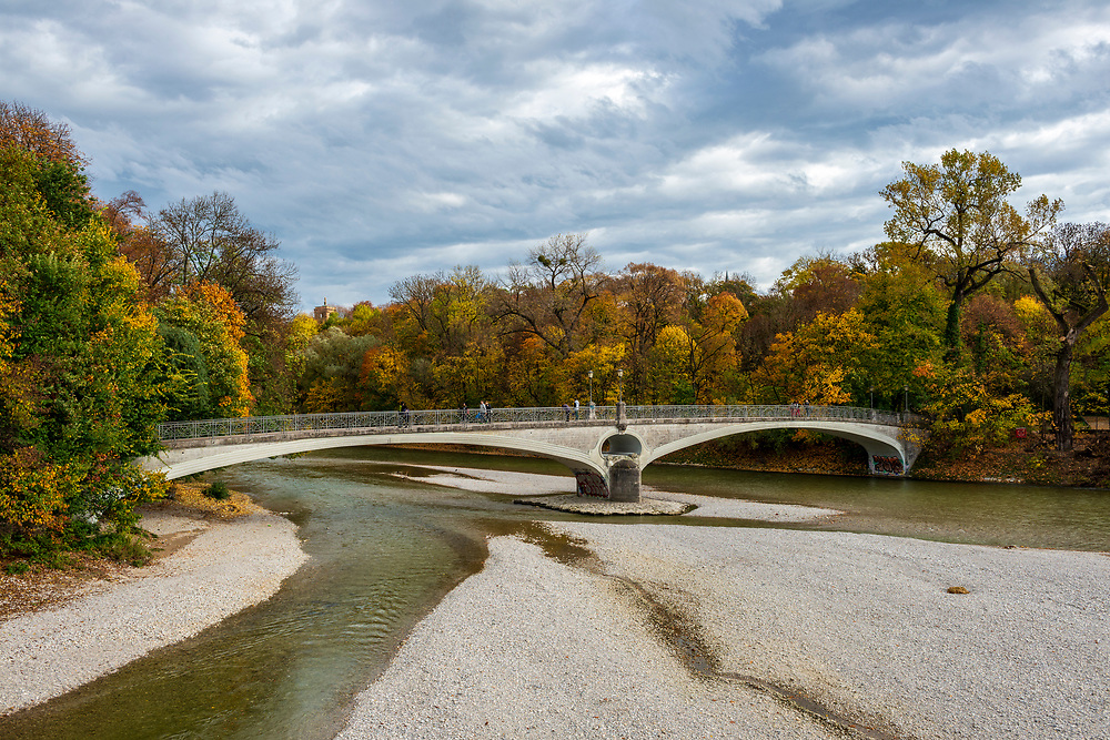 Munich, Germany - October 27, 2013: The Kabelsteg pedestrian bridge on a beautiful autumn afternoon in Munich, Germany. The bridge, built in 1898, connects the east bank of the Isar River with the Praterinsel and crosses the Isar branch known as the Kleine Isar.