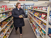 "25 FEBRUARY 2020 - BUTTERFIELD, MINNESOTA: KATIE HENDERSON, from St. James, MN., walks through the grocery section of the Butterfield True Value hardware store. She works in the Butterfield Post Office and came into the True Value to get some butter. Butterfield, MN, a farming community of about 500 people 130 miles southwest of the Twin Cities. The town has been a ""food desert"" for 10 years after its only grocery store closed in 2010. Barb Mathistad Warner and Mark Warner purchased the True Value store in Butterfield in December, 2018 and started selling groceries in the store in May, 2019. For residents of Butterfield going to a grocery store meant driving 10 miles to St. James, MN, or 20 miles to Windom, MN, the two nearest communities with grocery stores. The USDA defines rural food deserts as having at least 500 people in a census tract living 10 miles from a large grocery store or supermarket. There is a convenience store in Butterfield, but it sells mostly heavily processed, unhealthy snack foods that are high in fat, sugar, and salt.   PHOTO BY JACK KURTZ"