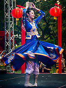 25 JANUARY 2017 - BANGKOK, THAILAND:        A Chinese dancer spins with bowls balanced on her head during Chinese New Year, also called Tet, celebrations in Lumpini Park in Bangkok. 2017 is the Year of the Rooster in the Chinese zodiac. This year's Lunar New Year festivities in Bangkok were toned down because many people are still mourning the death Bhumibol Adulyadej, the Late King of Thailand, who died on Oct 13, 2016. PHOTO BY JACK KURTZ