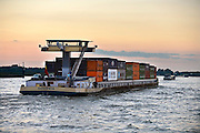 Nederland, Waal, 11-9-2014 Verkeer van binnenvaartschepen op de waal, rijn, richting het duitse ruhrgebied. Een containerschip bij ondergaande zon, avondzon. Foto: Flip Franssen/Hollandse Hoogte