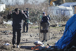 Calais, France. 04/03/16. A refugee walks past a line of French riot police who are cordoning off the demolition zone. French authorities are clearing the southern half of the Calais 'Jungle' camp, which charities estimate to contain 3,500 people.
