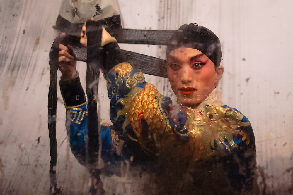 A Chinese opera singer adjusts his hairband in front of a stained mirror backstage, Chengdu, China. Photo ©Robert van Sluis - www.robertvansluis.com