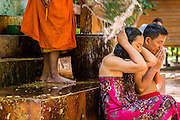 """02 JULY 2013 - ANGKOR WAT, SIEM REAP, SIEM REAP, CAMBODIA:  A Buddhist monk blesses a couple by splashing water on them at a small monastery near the Bayon temple in the Angkor Wat complex. Angkor Wat is the largest temple complex in the world. The temple was built by the Khmer King Suryavarman II in the early 12th century in Yasodharapura (present-day Angkor), the capital of the Khmer Empire, as his state temple and eventual mausoleum. Angkor Wat was dedicated to Vishnu. It is the best-preserved temple at the site, and has remained a religious centre since its foundation– first Hindu, then Buddhist. The temple is at the top of the high classical style of Khmer architecture. It is a symbol of Cambodia, appearing on the national flag, and it is the country's prime attraction for visitors. The temple is admired for the architecture, the extensive bas-reliefs, and for the numerous devatas adorning its walls. The modern name, Angkor Wat, means """"Temple City"""" or """"City of Temples"""" in Khmer; Angkor, meaning """"city"""" or """"capital city"""", is a vernacular form of the word nokor, which comes from the Sanskrit word nagara. Wat is the Khmer word for """"temple grounds"""", derived from the Pali word """"vatta."""" Prior to this time the temple was known as Preah Pisnulok, after the posthumous title of its founder. It is also the name of complex of temples, which includes Bayon and Preah Khan, in the vicinity. It is by far the most visited tourist attraction in Cambodia. More than half of all tourists to Cambodia visit Angkor.         PHOTO BY JACK KURTZ"""