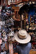 8 year old child wearing Akubra hat, looking at souvenir stall in market. Waikiki, Honolulu, Hawaii