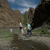 """Hikers descend Yolyn Am, a canyon called """"The Vulture's Mouth"""" in the Gobi Desert, Mongolia."""