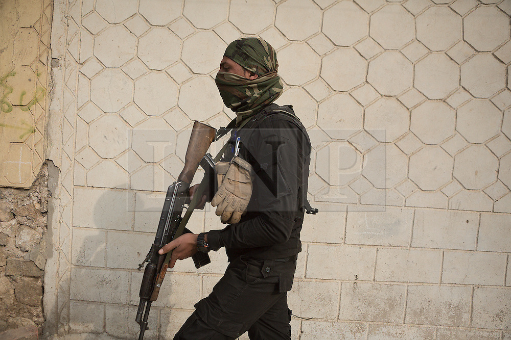 Licensed to London News Pictures. 13/02/2017. Mosul, Iraq. An Iraqi NSS officer, his face covered to protect his identity, holds his weapon at the ready as he approaches the home of a suspected ISIS member in a Mosul neighbourhood.<br /> <br /> The Jihaz Al-Amin Al-Watani, roughly translated as the National Security Service or NSS, are a secretive Iraqi agency that works under the responsibility of the Ministry of Interior. Since the liberation of eastern Mosul in January 2017 the NSS have been actively hunting down ISIS members who stayed behind to continue terrorism as part of sleeper cells and residents who worked with the group during its two year occupation. Recruiting from across the country agency is responsible for internal security inside Iraq and has a broad remit to investigate and arrest everything from terrorists and foreign spies to financial criminals and drug traffickers. Photo credit: Matt Cetti-Roberts/LNP