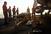 Red shirted ordnance men prepare and fit smart bombs to an F/A-18 fighter jet on deck of USS Harry S Truman. Launched on 7 September 1996 and costing US$4.5 billion, the Truman (CVN-75) is the eighth Nimitz-class supercarrier of the United States Navy, named after the 33rd President of the United States, Harry S. Truman. The Truman is the largest of the US Navy's fleet of new generation carriers, a 97,000 ton floating city with a crew of 5,137, 650 are women.