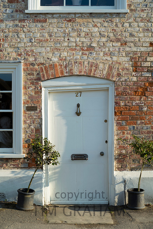 Quaint door painted white of brick built typical English cottage with bay trees in Ramsbury, Wiltshire, UK