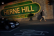 A pedestrian walks beneath the large sign under the railway bridge announcing Herne Hill, Lambeth SE24 south London. The mural is one of many in south London by the artist Lionel Stanhope.