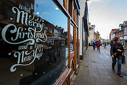 © Licensed to London News Pictures. 15/12/2020. RICKMANSWORTH, UK. A woman wearing a facemask walks by a Christmas message displayed in a shop window in Rickmansworth, Hertfordshire.  The historic town will be elevated to Tier 3 Covid Alert Level tomorrow, as part of the Three Rivers District Council area joining London and other areas of the South East as the number of coronavirus cases continues to rise. Health professionals have said that relaxing restrictions over the Christmas period will lead to increased number of Covid-19 related deaths.  Photo credit: Stephen Chung/LNP