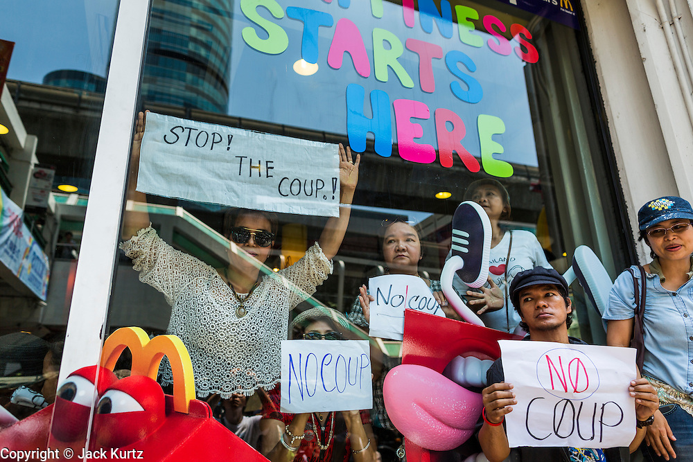 25 MAY 2014 - BANGKOK, THAILAND: Thais stand in the window with anti-coup signs during a protest at a McDonald's in Bangkok. Public opposition to the military coup in Thailand grew Sunday with thousands of protestors gathering at locations throughout Bangkok to call for a return of civilian rule and end to the military junta.     PHOTO BY JACK KURTZ