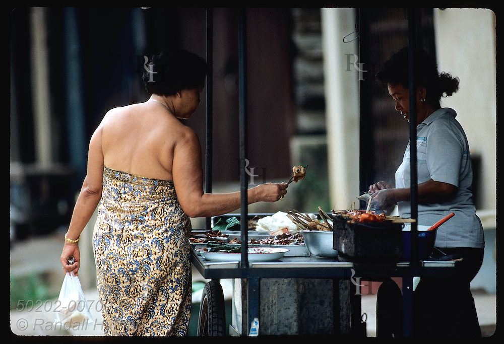 Woman in sarong buys snack from street vendor in Krabi.  Thailand