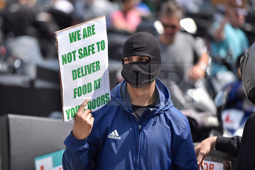 © Licensed to London News Pictures. 18/07/2017. London, UK. Moped riders stage a protest in Parliament Square demanding that the government act on moped thefts in the light of recent acid attacks by assailants riding stolen mopeds.  Many of the protesting riders work for food delivery companies. Photo credit : Stephen Chung/LNP