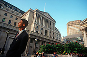 A 1990s businessman stands beneath the tall architecture of the Bank of England, in the City of London aka The Square Mile, the capitals financial centre, on 21st June 1997, in London, England.