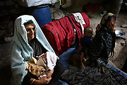 Women and children, including Khalisa, at left with a baby, the mother-in-law of Qamar, a 26-year-old tuberculosis patient who died of postpartum complications two weeks after the delivery, return to their normal life the day after the funeral in their house, Shohada district in Badakshan province, Afghanistan, Tuesday, May 22, 2007.