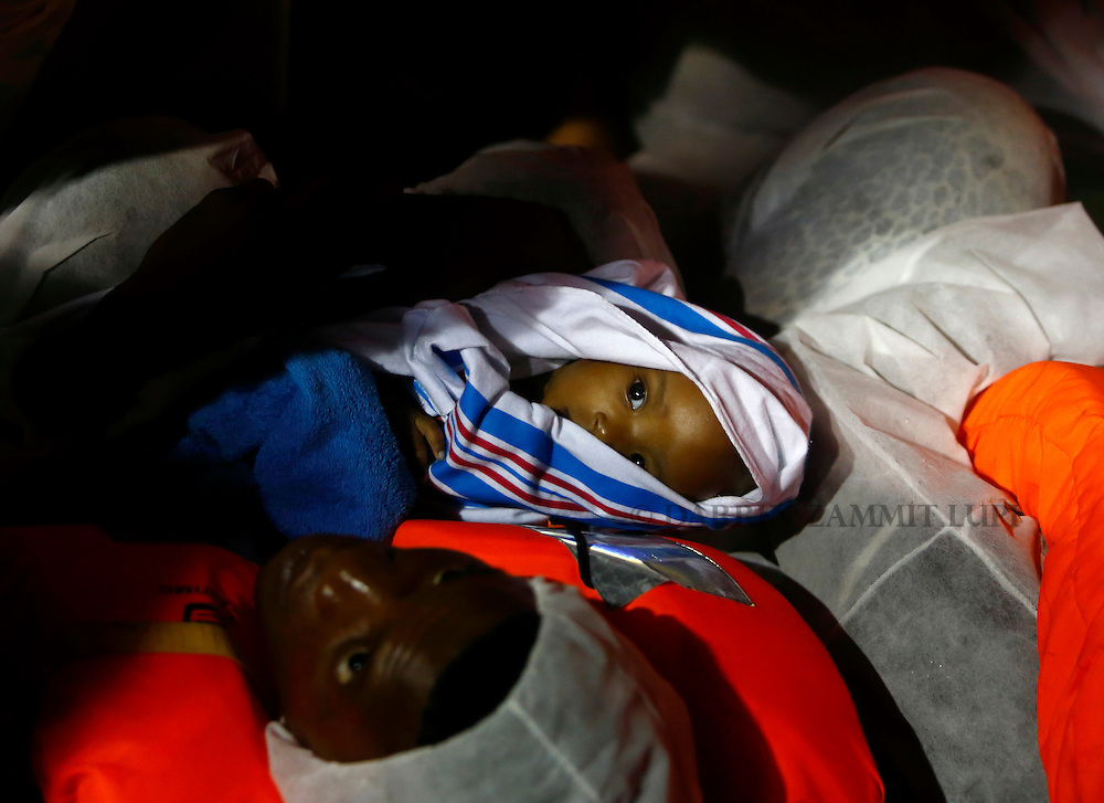 A migrant carries his baby on a Migrant Offshore Aid Station (MOAS) RHIB (rigid hulled inflatable boat) alongside the MOAS ship MV Phoenix before being transferred to the Norwegian ship Siem Pilot off the coast of Libya August 6, 2015.  An estimated 700 migrants on an overloaded wooden boat were rescued 10.5 miles (16 kilometres) off the coast of Libya by the international non-governmental organisations Medecins san Frontiere (MSF) and MOAS without loss of life on Thursday afternoon, according to MSF and MOAS, a day after more than 200 migrants are feared to have drowned in the latest Mediterranean boat tragedy after rescuers saved over 370 people from a capsized boat thought to be carrying 600.<br /> REUTERS/Darrin Zammit Lupi <br /> MALTA OUT. NO COMMERCIAL OR EDITORIAL SALES IN MALTA