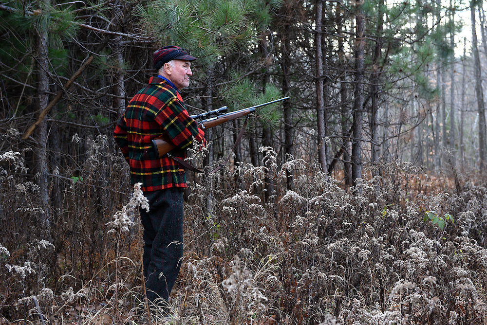 Bernie Corrette, of Lebanon, pauses to load his rifle on his way into the woods to hunt in Lebanon, N.H. Tuesday, November 24, 2015.  (Valley News - James M. Patterson)<br /> Copyright © Valley News. May not be reprinted or used online without permission. Send requests to permission@vnews.com.