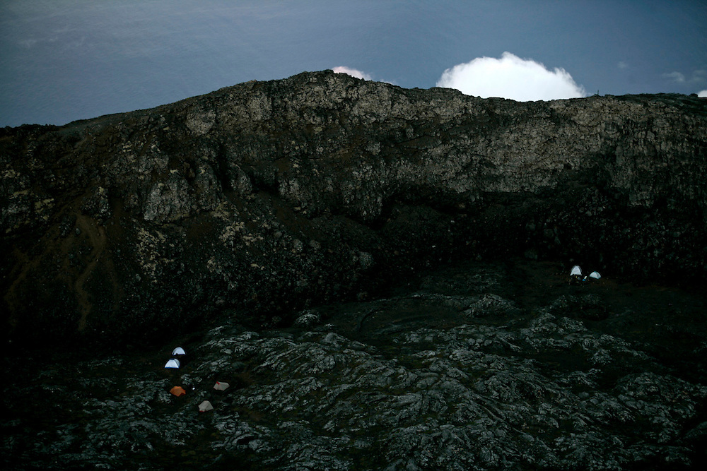 The surrounding view from  Pico mountain's summit includes a view from the dormant volcano crater. Usually is where people mount their tents . Just up the crater wall  Atlantic ocean  can be seen in this picture.