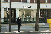 """March, 27th 2020 - Paris, Ile-de-France, France: Paris under confinement, Loewe, Avenue Montaigne area of high fashion, beauty, accessories, haute couture, all shops closed, in 8th arrondissement, and all public spaces virtually empty to stop the spread of the Coronavirus, during the eleventh day of near total lockdown imposed in France. The President of France, Emmanuel Macron, said the citizens must stay at home for at least 15 days, that has been extended. He said """"We are at war, a public health war, certainly but we are at war, against an invisible and elusive enemy"""". All journeys outside the home unless justified for essential professional or health reasons are outlawed. Anyone flouting the new regulations is fined. Nigel Dickinson"""