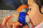 young girl of two feeds off a bottle