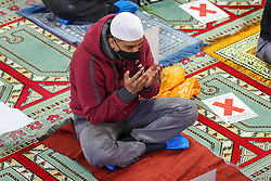 © Licensed to London News Pictures. 24/04/2021. London, UK. A muslim devotee wearing a face covering attend Friday prayers during the Islamic holy month of Ramadan at the London Islamic Cultural Society and Mosque, also known as Wightman Road Mosque in Haringey, north London. The devotees are two meters apart and keeping to the rules of social distancing following the Covid-19 outbreak. Muslims across the world are observing the holy fasting month of Ramadan, a month long celebration with prayers, readings from the Koran and gatherings with family and friends, as they abstain from eating, drinking and smoking from dawn till dusk. Photo credit: Dinendra Haria/LNP