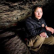 Young Mongolian woman crouches inside cave (Gorkhi-Terelj national park, Mongolia - Sep. 2008) (Image ID: 080917-1543121a)