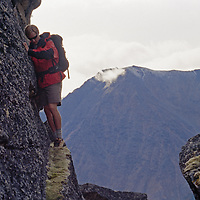 A hiker inches across a ledge on a huge boulder.