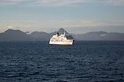 Cruise ship passing mountains of Lofoten Islands, Nordland, Norway