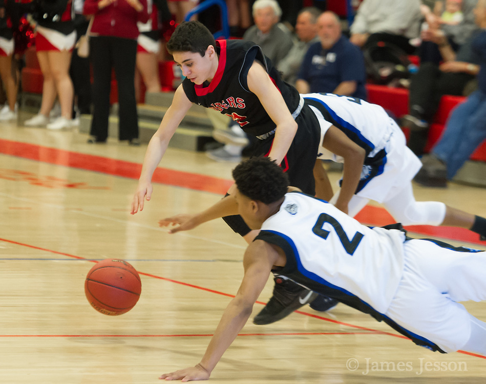 Watertown High School freshman Gabe Spinelli chases after the ball with  Jeremiah E. Burke High School junior Levar Williams during the MIAA Division 3 state semifinal game in Burlington, March 14, 2018. The Raiders won the game, 66-61. [Wicked Local Photo/James Jesson]