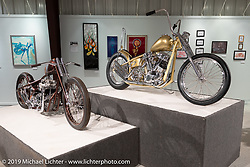 138 Cycle Fabrication's Cole Rogers' Rocket to Russia (L) custom 1970 Triumph tribute to his late father and Dakota Toomey's Mind Control Zenith Gold 1960's showbike style 1956 Panhead chopper on view in the What's the Skinny Exhibition (2019 iteration of the Motorcycles as Art annual series) at the Sturgis Buffalo Chip during the Sturgis Black Hills Motorcycle Rally. SD, USA. Friday, August 9, 2019. Photography ©2019 Michael Lichter.