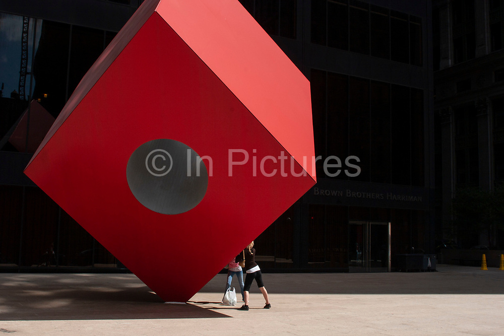 People pretend to support public art scuplture Red Cube 1968 by artist Isamu Noguchi situated at 140 Broadway, between Liberty Street and Cedar Street on 20th May 2007 in New York City, United States.
