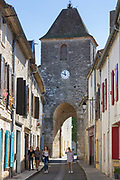 Tourists by 13th Century medieval gateway clock tower in ancient bastide fortified town of Duras in Aquitaine, France