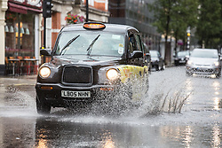 © Licensed to London News Pictures. 26/07/2015. London, UK. A london cab drives through a flooded road in central London.  Photo credit : James Gourley/LNP