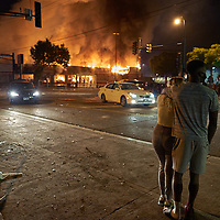 Protesters gather to watch a n Advance Auto Parts store burning near the Minneapolis Police third precinct after a white police officer was caught on a bystander's video pressing his knee into the neck of African-American man George Floyd, who later died at a hospital, in Minneapolis, Minnesota, U.S. May 28, 2020. REUTERS/Adam Bettcher