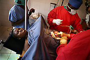 Dr. Philip Dirksen, far right, an American doctor from Sacramento, Calif., along with Congolese doctors and nurses, performs the operation of a victim of sexual violence at Gesom Hospital, in Goma, North Kivu province, Monday, March 10, 2008. The doctor said the patient's urethra had been severely damaged by the rape, and despite her first operation, she was unable to control her urine. He performed the surgery that day to open her abdomen, and connect the tubes from the kidney to the colon, which at least would make her continent.
